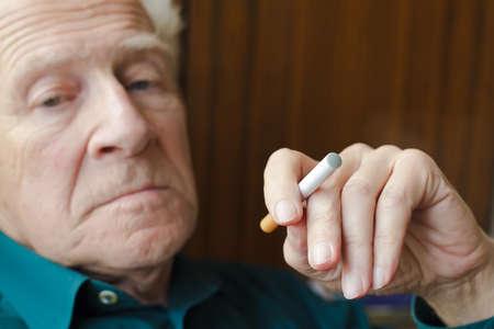 close-up senior man holding electronic cigarette, focus is on the e-cigarette Banque d'images