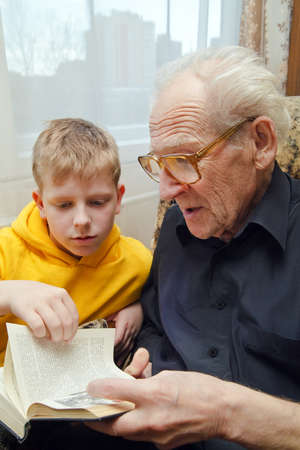 grandfather reading book aloud to his grandson, who is listening to him with attention Stock Photo - 9757963