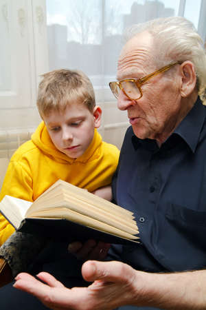 grandfather reading book aloud to his grandson, who is listening to him with attention Stockfoto