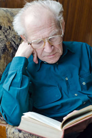 grave old man in glasses reading a book, holding his head photo