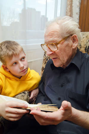 two story: grandfather reading book aloud to his grandson, who is listening to him with attention Stock Photo