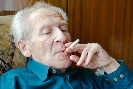 thoughtful senior man smoking electronic cigarette photo