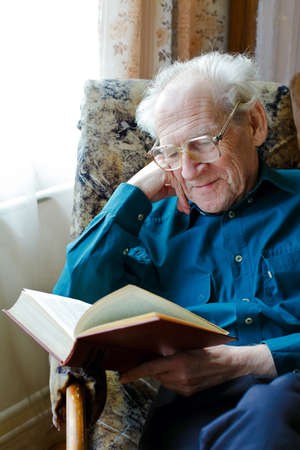 smiling old man in glasses reading a funny book, holding his head Stock Photo