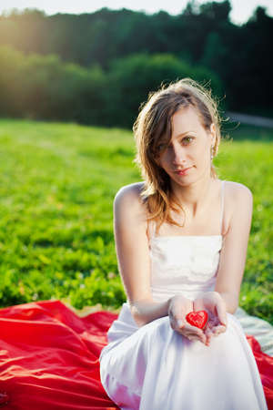 newlywed woman holding in her hands red heart - symbol of love photo