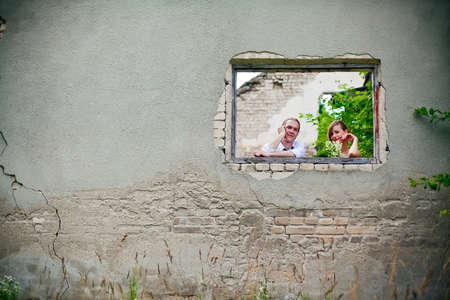 portrait of a couple, they are standing at the window of old building photo