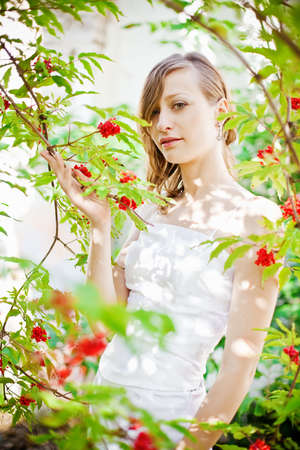 portrait of a pretty bride standing near the tree with red berries photo
