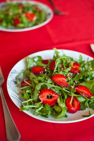 close-up salad with fresh strawberries, arugula and sunflower seeds Stockfoto