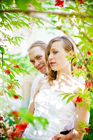 portrait of a bride and groom standing near the tree with red berries photo