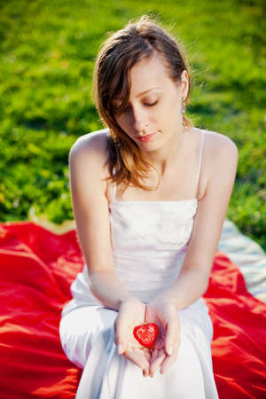 bride holding in her hands red heart - symbol of love photo