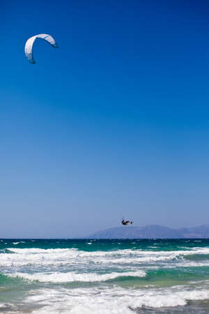 unrecognizable man surfing on waves with kite photo