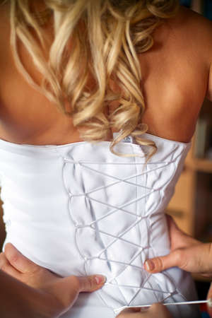 the back of blonde bride in white corset, bridesmaid is helping her to dress photo