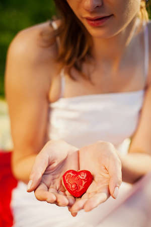 woman holding red heart in her hands - symbol of love photo