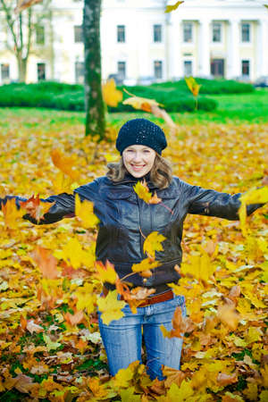enjoymant: Young laughing woman playing with the falling leaves Stock Photo