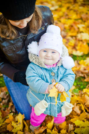 Young mother with her little laughing girl in a beautiful park in autumn photo