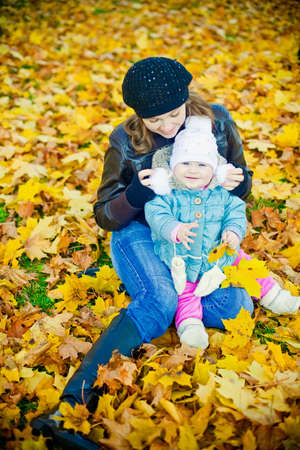 Young mother with her little smiling daughter in a beautiful park in autumn photo