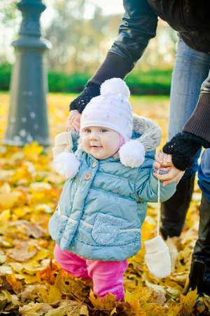 Mother helping her daughter with her first steps in the park in autumn Stock Photo