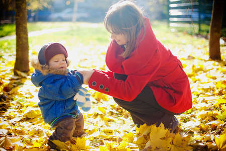 Young mother playing with her little smiling son in a yellow park in autumn photo