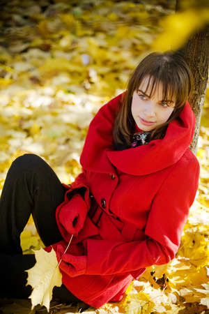 young beautiful woman sitting under autumn maple tree with a leaf in her hands  photo