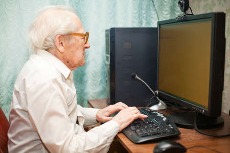 portrait of a senior man typing something on his computer Stock Photo