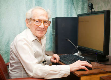 old man portrait: smiling happy old man sitting near computer and holding mouse Stock Photo