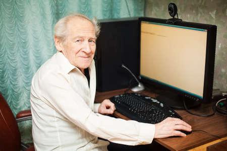 senior ordinateur: sourire vieil homme tenant la souris d'ordinateur - il travaille sur un ordinateur de bureau