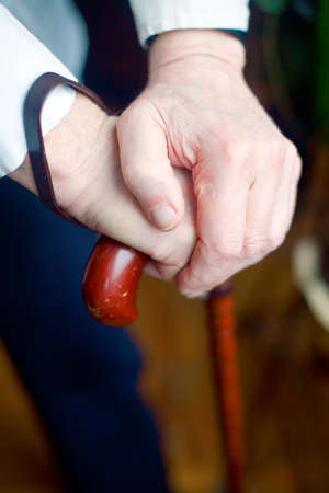 close-up of senior mans hands holding his cane photo