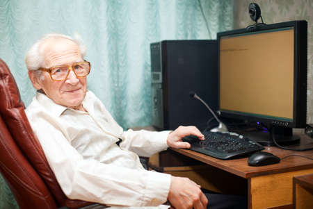 smiling pleased old man sitting near computer - he is working Stock Photo