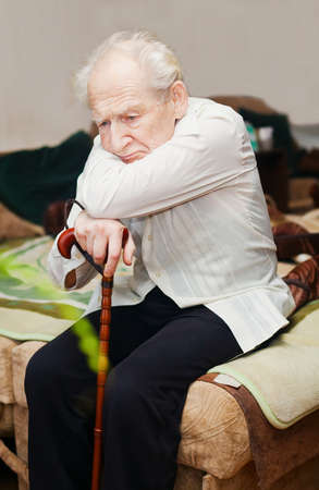 sad lonely old man sitting with his cane
