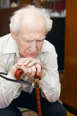 infeliz de edad sosteniendo su bastón