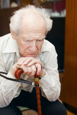 unhappy old man holding his cane
