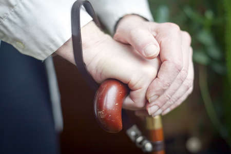 close-up of senior mans hands holding his cane