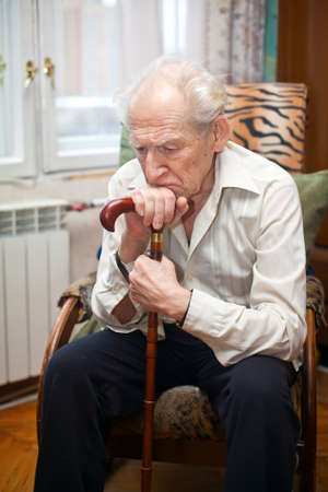 sad lonely old man sitting in an armchair with his cane photo