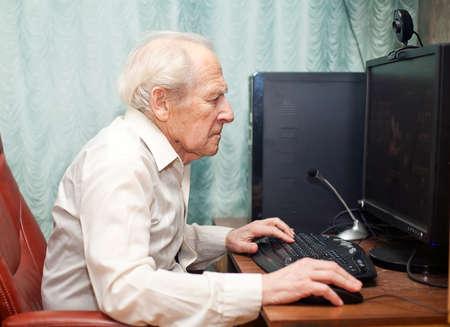 ordinateur bureau: portrait d'un homme �g� tape quelque chose sur son ordinateur Banque d'images