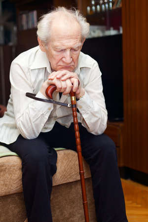 unhappy old man sitting on a bed and holding his cane