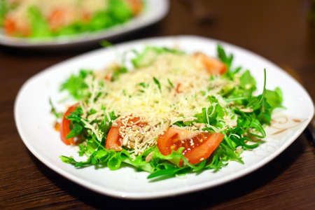 close-up fresh salad with lettuce, arugula, tomatoes, sunflower seeds, parmesan and sesame photo