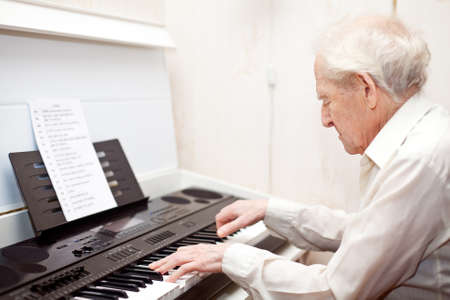 grey-haired senior man playing piano photo