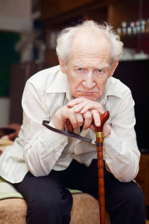 unhappy old man sitting on a bed and holding his cane photo