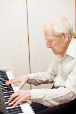serious senior man playing piano photo