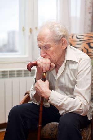 traurige einsame alte Mann sitzt in einem Sessel mit seinem Stock Standard-Bild