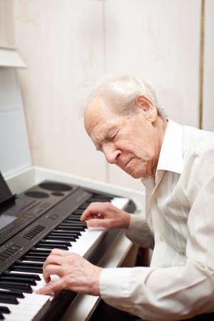 tocando piano: hombre mayor con los ojos cerrados a tocar el piano Foto de archivo