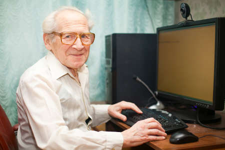 old business man: smiling happy old man sitting near computer and holding mouse Stock Photo