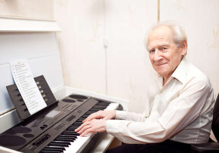 smiling pleased senior man playing piano