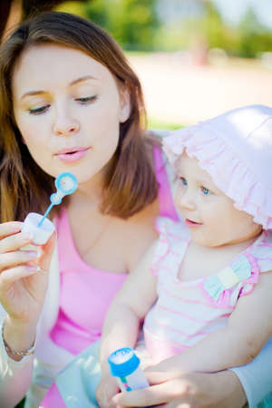 mother blowing soup bubbles - her daughter looking with smiling Stock Photo