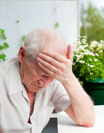 face portrait of an old senior man, he has a headache, his hand on his forehead Stockfoto