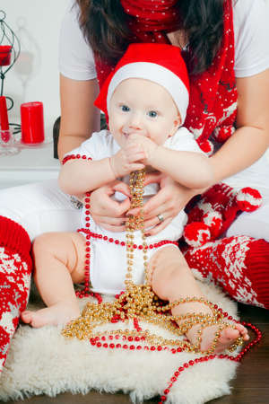 mother holding her little son, it is Christmas time, the boy wearing Santa's hat Stock Photo - 16192432
