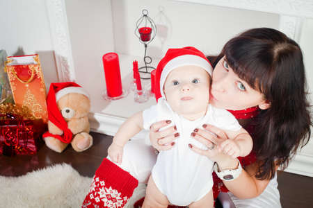 young mother kissing her little son, the boy is in Santa's cap Stock Photo - 16192434