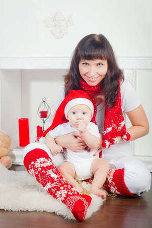 smiling mother holding her little son, it is Christmas time, the boy wearing Santa's hat Stock Photo - 16406178