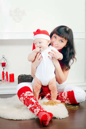 young mother with her little son in Santa's cap, it is Christmas time Stock Photo - 16672047