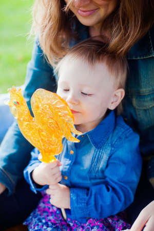 little girl holding a cockerel-shaped lollipop photo