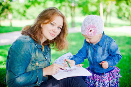 young mother and her little daughter sitting on a grass in the park and drawing something photo